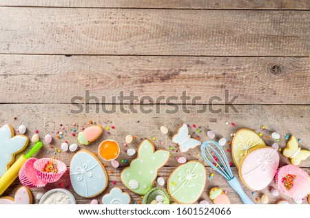 Easter cooking baking background with pastel colored easter cookies, sugar sprinkles and ingredients for bake cake and cookies.  Wooden rustic background, flatlay banner copy space