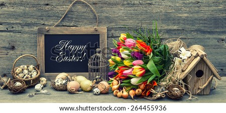 Easter decoration with eggs and tulip flowers. Vintage background with sample text Happy Easter! Retro style toned picture.
