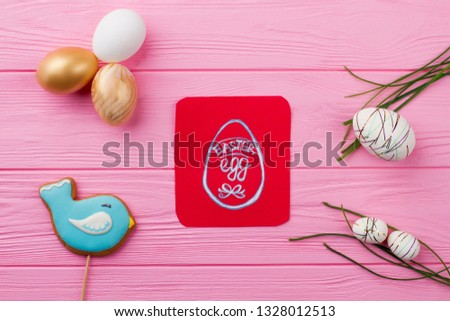Easter decoration with golden eggs. Easter delicious biscuit, modern styrofoam eggs and grass on wooden table. Picture of Easter egg.