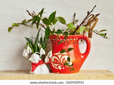 Easter decoration with red mug, lamb and flowers