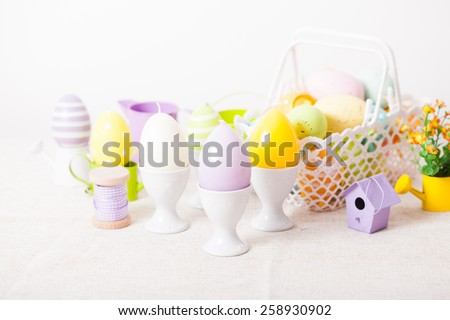 Easter decorations - egg candles, nest and flowers on the table