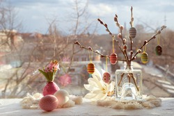 Easter decorations on windowsill in Spring. Wooden painted eggs on pussy willow twigs, Easter eggs, hyacinth with bulbs in wax, macrame mats. Window with urban view on sunset. Happy Easter