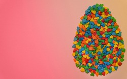 Easter Egg form from colorful heart shape sweet candy on graduated pink and yellow colored background. Happy Easter Day card concept. Copy space for text. Minimal concept.