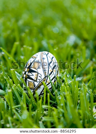 Easter egg, handpainted with the symbol of the cross, on bright green dewey grass.  Shallow depth of field, ample copy space