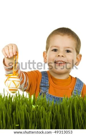 Easter egg hunt, boy searching for easter eggs hidden in fresh green grass