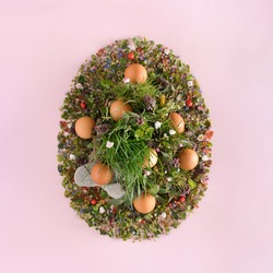 Easter egg made of flower and grass. Creative holliday decoration on pastel pink background.