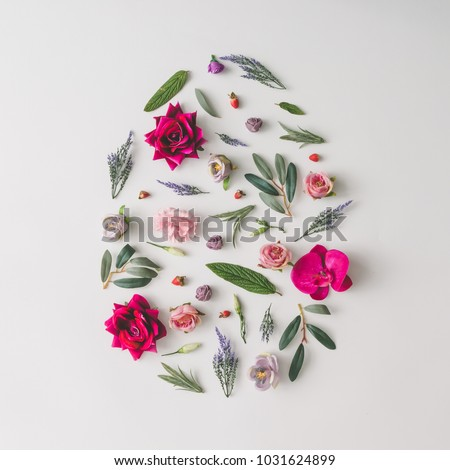 Easter egg shape made of colorful spring flowers and green leaves.  Minimal holiday concept. Flat lay pattern.