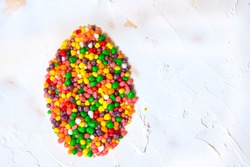 Easter egg shape made of rainbow colored candy nerds. Flat lay. Copy space.