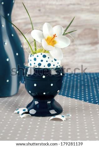 Easter egg vase with open white crocus flower on neutral background