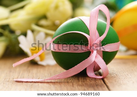 Easter egg with bows over floral background