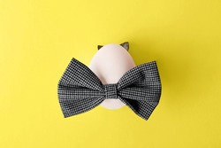 Easter egg with grey bow tie and ears from natural laves on the trendy yellow color 2021.Minimal concept.Holiday background,copy space.
