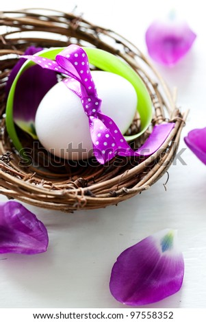 easter egg with ribbon in a nest