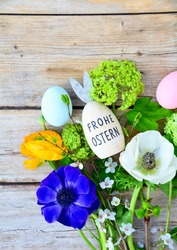 Easter egg with text in German and spring flowers on a rustic wooden background - Frohe ostern means happy Easter