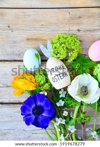 Easter egg with text in German and spring flowers on a rustic wooden background - Frohe ostern means happy Easter Stock foto ©
