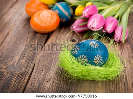 Easter egg with tulips on wooden background