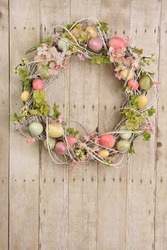 Easter egg wreath on a wooden background. Also available in horizontal.