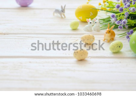 Easter eggs and branch with flowers on wooden. Rabbits toys. #1033460698