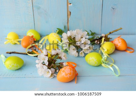 Easter Eggs and cherry blossoms on a  wooden background. Easter decoration  #1006187509