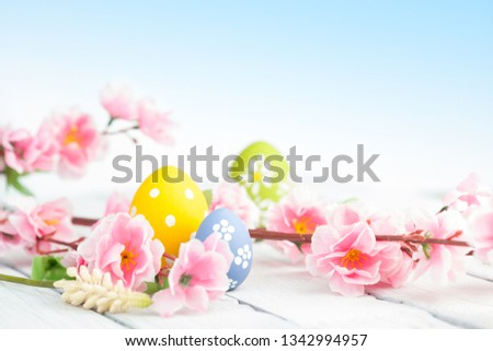 Easter eggs and pink flowers decoration on blue background. Gentle toned picture #1342994957