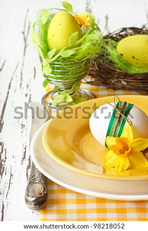 Easter eggs and spring flower on a white wooden board.