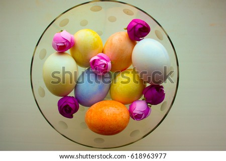 Easter eggs are tender in a glass vase glass in polka dots with flowers buds of roses. Photo for your design. #618963977