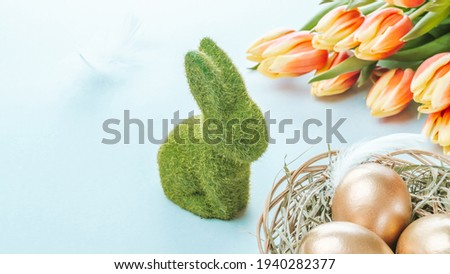 Easter eggs basket. Golden egg in basket with spring tulips, white feathers on pastel blue background in Happy Easter decoration. Traditional decoration in sun light Foto stock ©