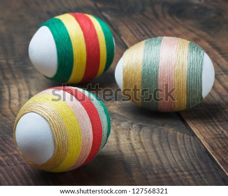 Easter eggs decorated with woolen threads on a wooden table