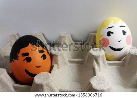 Easter eggs emoticons. Brown and white eggs boy and girl with painted emotions smiling faces looking with interest at each other. Easter in mixed multicultural families. Interracial relations