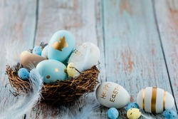 Easter eggs, feathers in a nest on a blue wooden background. The minimal concept of Easter. An Easter card with a copy of the place for the text.