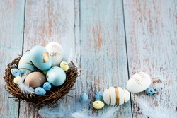 Easter eggs, feathers in a nest on a blue wooden background. The minimal concept of Easter. Top view. An Easter card with a copy of the place for the text.