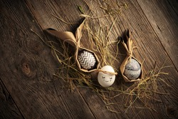 Easter eggs, festive card, Stylish packaged monochrome eggs lying on wooden backdrop with hay. Ecofriendly holiday