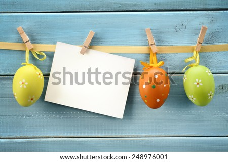 Easter eggs hanging on wood background with blank card.