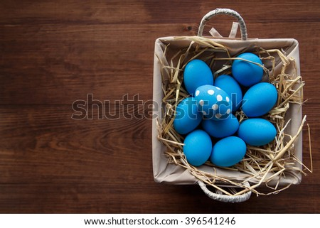 Easter eggs  in a basket on rustic wooden background, selective focus image, Happy Easter!