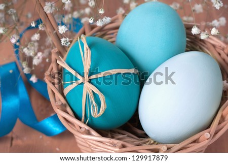 Easter eggs in a basket on wooden background