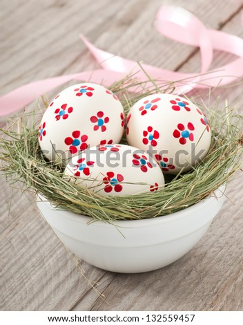 Easter eggs in a bowl decorated with a nest on the wooden table