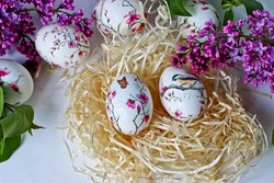 Easter eggs in a decorative nest with lilac on a marble background