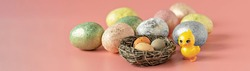 Easter eggs in a natural nest with bird eggs. Painted eggs and a decorative chicken on a pink background of pastel colors. Banner.Selective focus