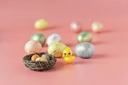 Easter eggs in a natural nest with bird eggs. Painted eggs and a decorative chicken on a pink background of pastel colors. Selective focus.