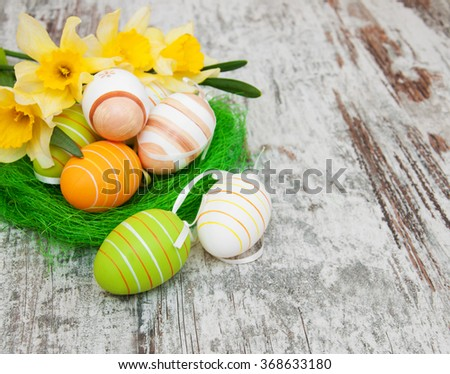 easter eggs in a nest with daffodil flowers on a old wooden background #368633180
