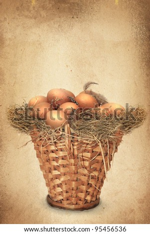 Easter eggs in a wooden basket on paper texture or background - stock photo