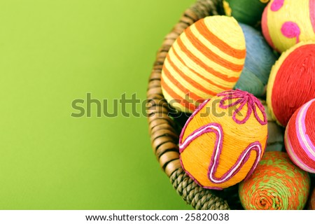 Easter eggs in basket on green background