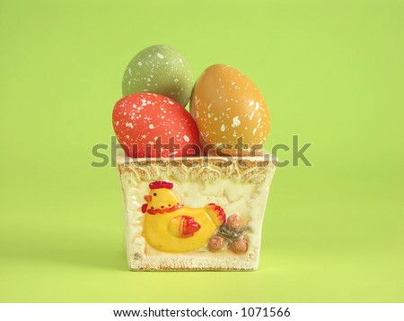 Easter eggs in clay pot over light green background