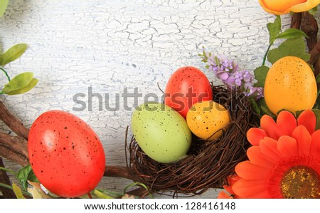 Easter eggs in nest on a weather wooden background. Also available in vertical.
