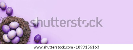 Easter eggs in nest on purple background. Flat lay, top view. Foto stock ©