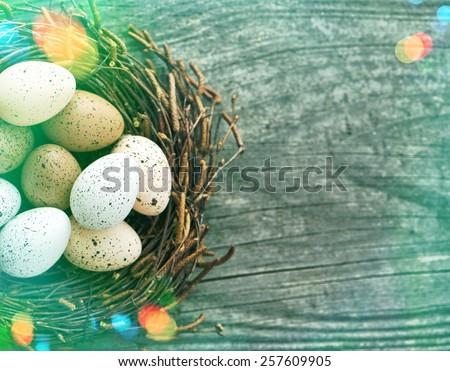 Easter eggs in nest on wooden background. Retro style toned picture with light leaks #257609905