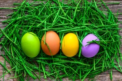 Easter eggs in nest with green grass, spring vibrant color eggs