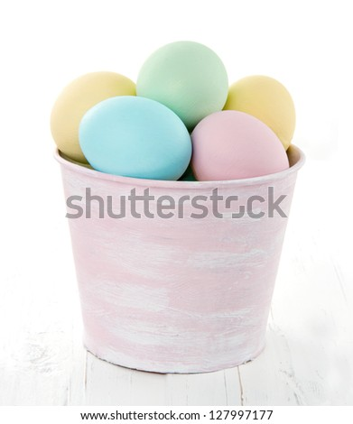 Easter eggs in pink decorative bucket on white wooden background