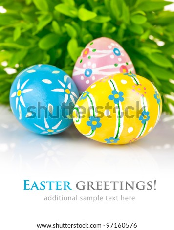 Easter eggs in the green grass isolated on white background