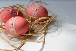Easter eggs in the nest in pink color and decoration for Easter card background