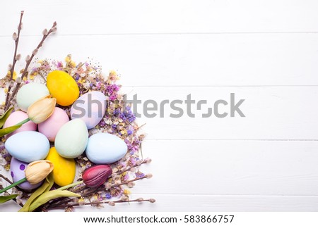 Easter eggs in the nest of dry twigs with flowers and place for text on a white wooden background